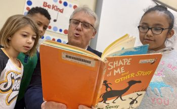 superintendent reading Dr. Seuss book to 3 elementary students
