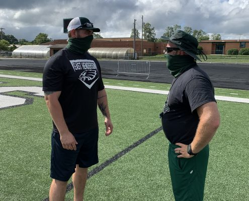 two coaches on field wearing masks