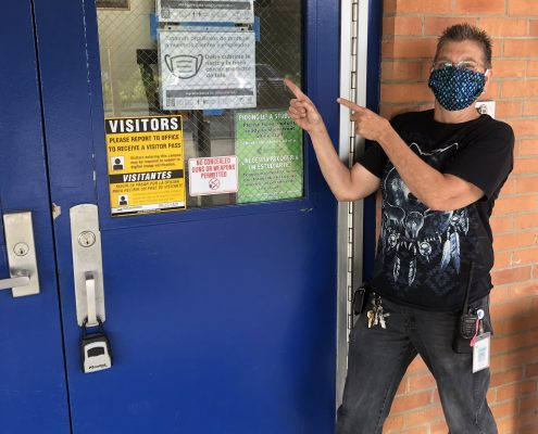 man wearing mask pointing to signs on door