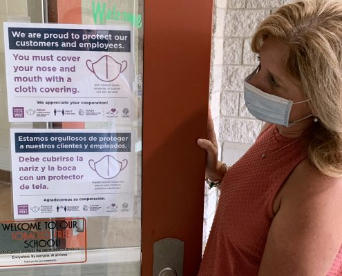 woman in mask next to door with signs