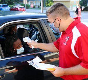 school staffmember taking temperature of a student through car window