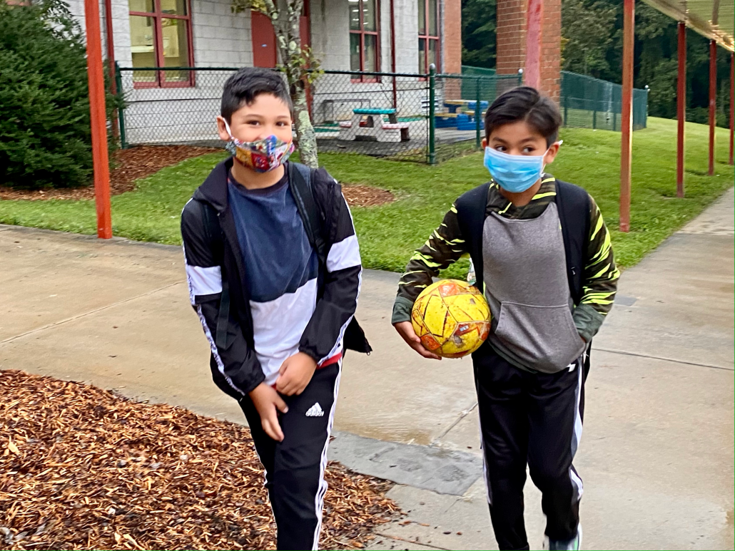 two boys wearing masks carrying soccer ball