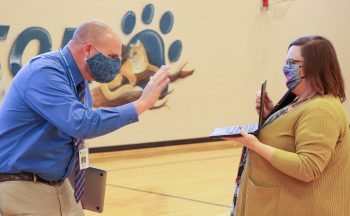 Principal Mark Page (L) waves to Atkinson staff and students who joined in virtually on the celebration, thanks to behind-the-scenes work from Amanda Childers, Small Schools Administrator.