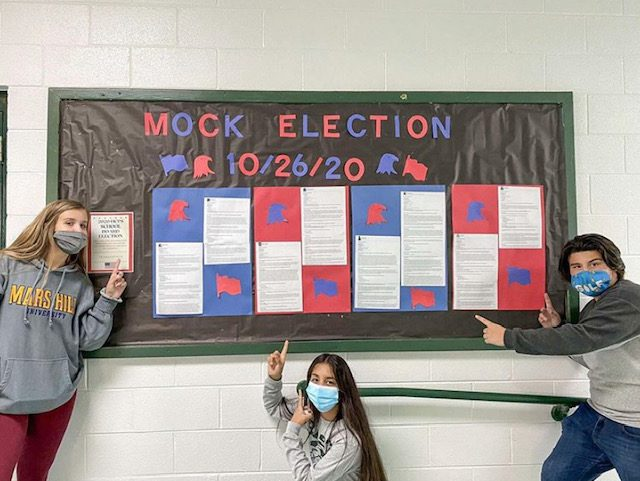 """three high school students pointing to bulletin board with """"Mock Election"""" on it"""