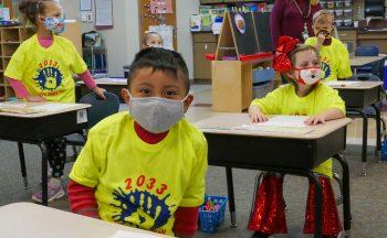 four kindergarteners at desks in neon shirts