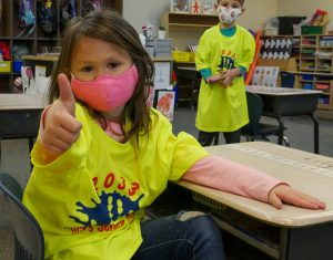 kindergartener in neon yellow shirt giving thumbs up