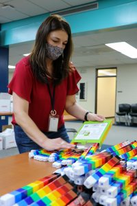 woman in mask organizing Unifix cubes