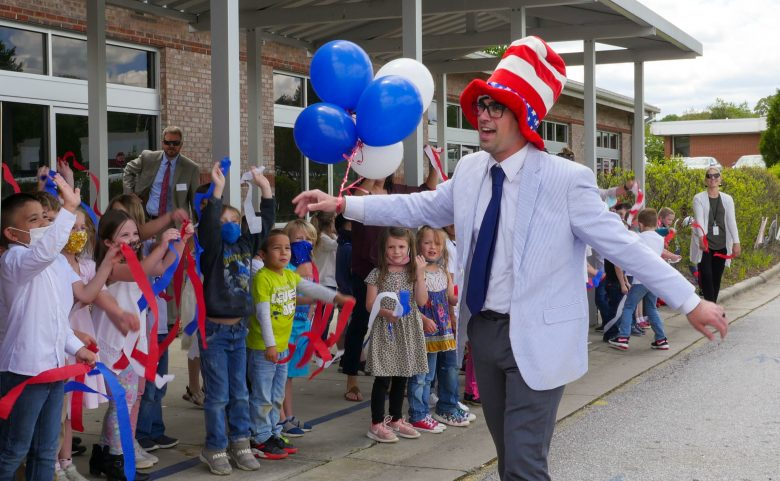 man in tall striped hat and balloons being cheered by students
