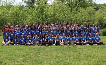 group of middle school girl athletes gathered outside in group picture