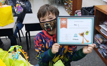student in face mask smiling, holding up certificate