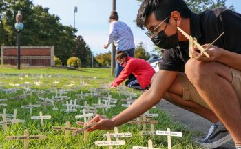 student placing small wooden crosses in grass