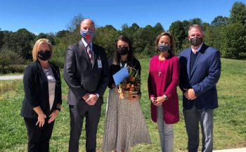 five people standing outside in masks