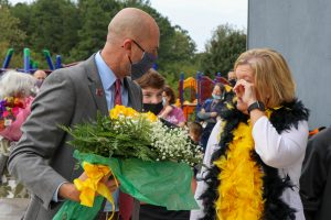 woman wiping tear from eye while man gives her flowers