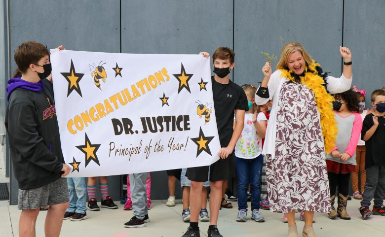 """two boys in masks hold sign that says """"congratulations dr. justice principal of the year"""" while woman does happy dance"""