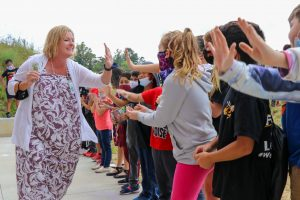 line of students reaching to high five principal