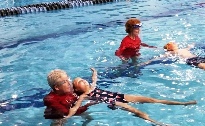 swim teacher helping a student float