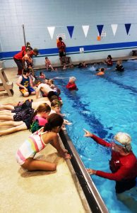 students lined up along edge of pool while instructor gives lessons