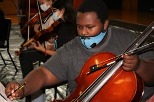 student with cello making notes on music